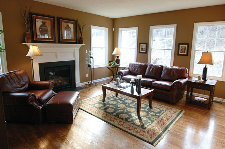 Great room furnished with stylish brown leather couch and chair