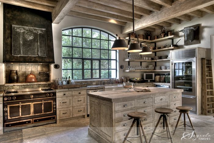This kitchen is perfection!  From the cabinets made of vintage French mercantile pieces and the reclaimed French limestone counters from Chateau Domingue to the La Cornue range and light fixture from Brown - absolutely amazing! I adore the industrial stools for the homeowner's three kids - they are so cute at all different heights!!