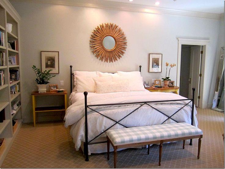 Sunburst mirror above bed. Master bedroom built ins. Bookshelves. Taupe and blue color scheme.