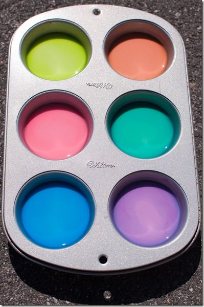 Sidewalk chalk paint is so much cooler than regular old sidewalk chalk!  It's 1 part cornstarch to 1 part water.  Once its all mixed up, I divided it among the 12 muffin cups, and added two drops of food coloring to each muffin cup.