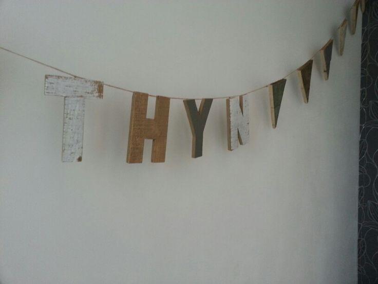 Houten vlaggenlijn met letters van Xenos en vlaggetjes van pallethout