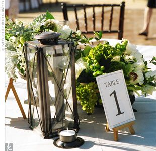 River rocks, lanterns, votives and overflowing white and green floral arrangements lined the head table.