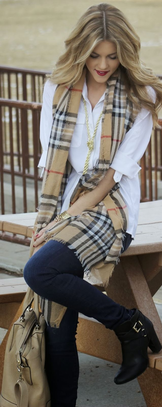 Fashionable look in white shirt scarf jeans pants and long boots