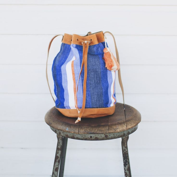 Gradient blue striped bucket bag with leather bottom and straps and