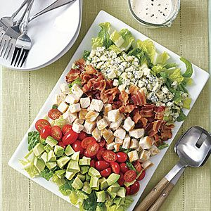 6 strips bacon $  1/2 cup plain yogurt (not nonfat) $  1 tablespoon lemon juice $  1 tablespoon olive oil $  1 clove garlic, finely chopped  1/2 teaspoon salt  2 romaine hearts, cut crosswise into half-inch strips $  2 cups diced cooked skinless rotisserie chicken  1 cup cherry tomatoes, halved $  1 ripe avocado, diced $  3 ounces blue cheese, crumbled