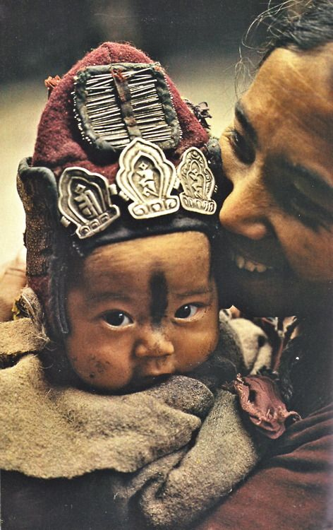 """March 1978 :: """"The woolen cap on a younger child guards against cold winds, while the amulets and needles that decorate it ward off evil spirits.""""    from Ladakh - The Last Shangri-la, article and photographs by Thomas J. Abercrombie"""
