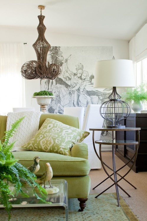 green couch, lucite coffee table, branch chandelier, art