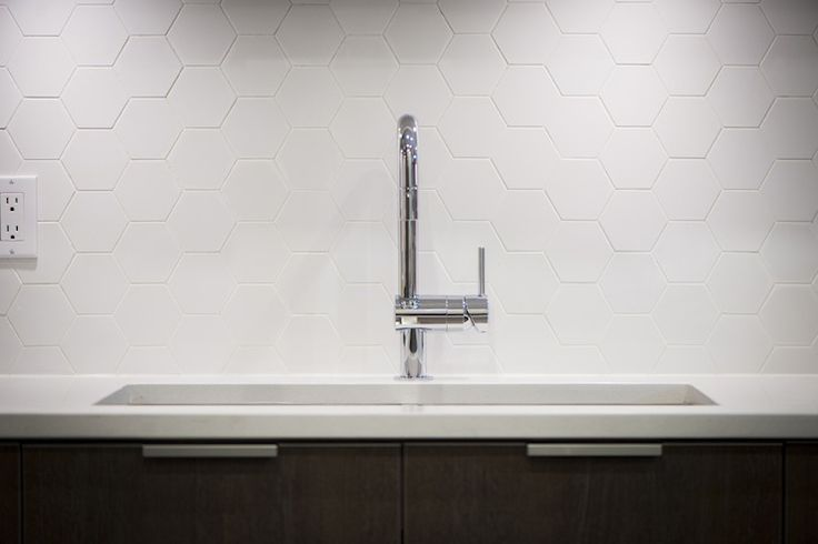hexagonal backsplash.....Portico Design Group ..,kitchen.... modern kitchen cabinets,gooseneck faucet, undermount sink, white countertop, pull tab hardware, white hexagonal backsplash tile, honeycomb tiles