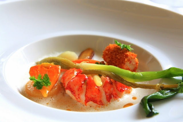 Lobster poached in butter with a braised green onion, root vegetables ...