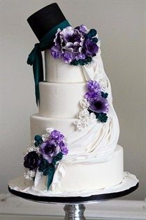 An elegant top hat, draped fondant and intricate purple and white flowers combine for a romantic, old-world wedding cake.