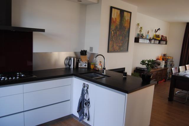 vb L vormige keuken, houten vloer, witte kastjes, zwart blad  New ...