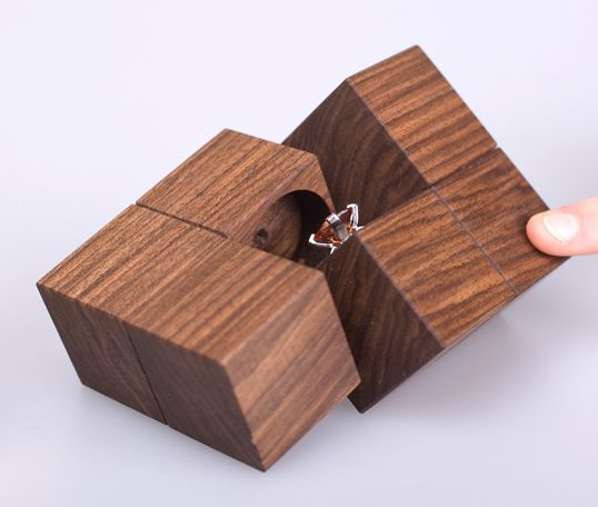 """This packaging is made of six identical wooden cubes made of oiled nutwood. A leather hinge provides the opening function, a paper loop is used as closure. KLOTZ is not only for protecting the jewelry, but also for presenting it! The whole packaging is made out of natural materials and is 100% biodegradable."""