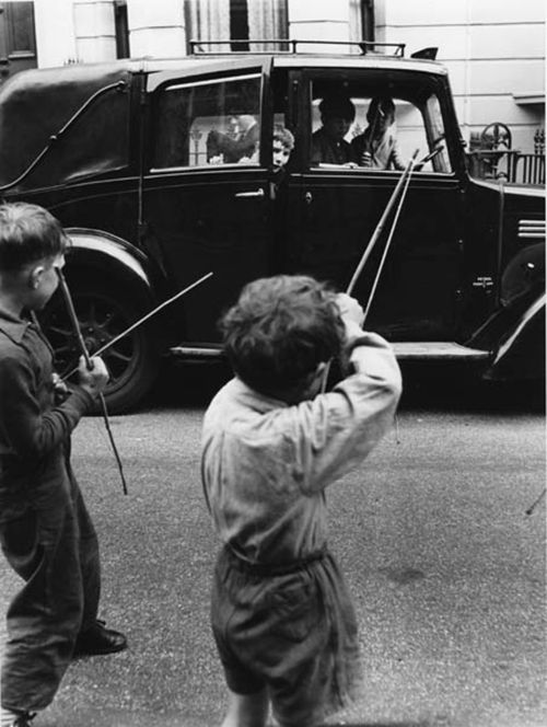 Boys playing with bows and arrows in a street. North Kensington, 1957.