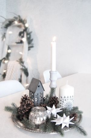 Scandinavian Christmas design with lots of white, clean lines, and a little zinc house. Centre de table pour un noël nature
