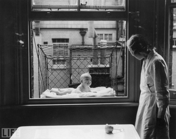 A baby suspended in a wire cage attached to the outside of a high tenement block window. The cages were distributed to members of the Chelsea Baby Club in London who have no gardens""