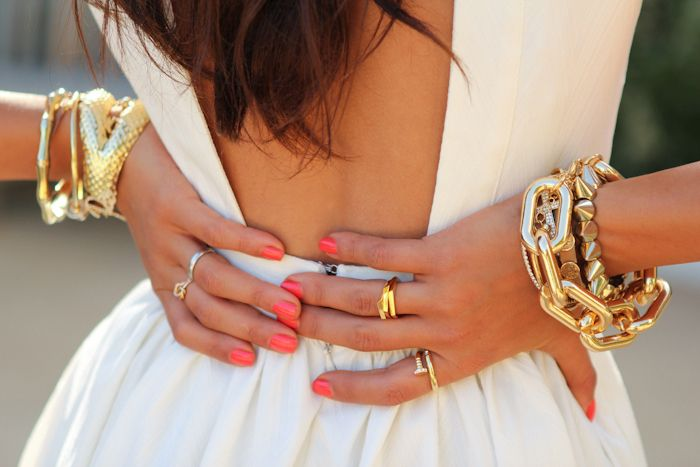 Coral nails and gold jewelry.