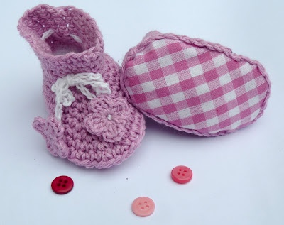 Ces petits chaussons crochetés en coton de couleur mauve sont idéals pour le printemps et l'été. Leurs petites semelles sont en tissu vichy assorti. Les cordelières blanches permettent aux chaussons de bien rester sur les pieds du bébé. Il s'agit d'une taille naissance.
