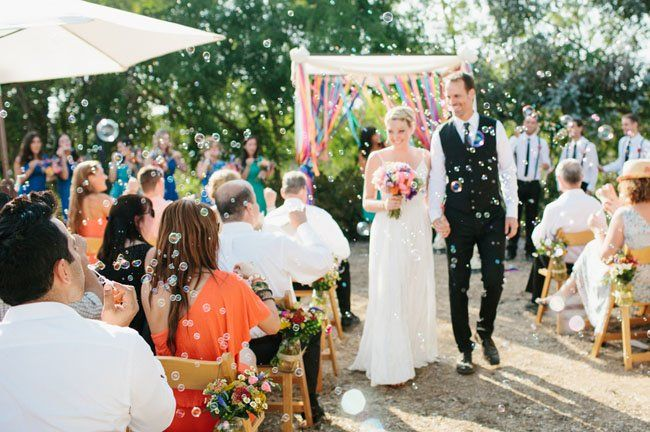 Love the casual backyard wedding ceremony with ribbon backdrop and
