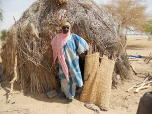 Fadimata Daouda, a Trickle Up participant from Mali, West Africa, poses in front of her home.