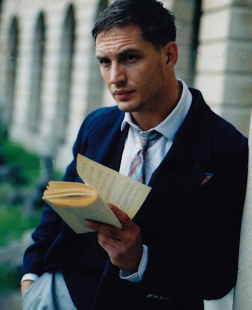 Tom Hardy breaks the spine of the Batm … um, book.  bookporn:    Handsome Tom Hardy torturing a book and reading it.