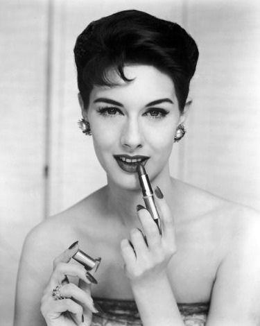 Nancy Berg applying lipstick, 1950s