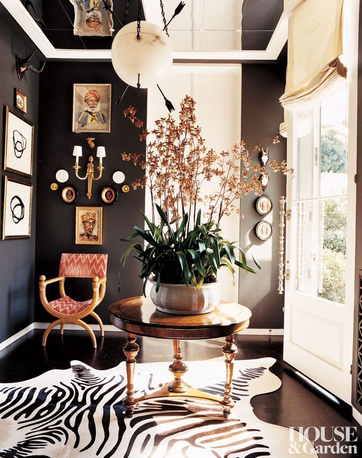In the vestibule of a California by Kelly Wearstler, the black wall paint was matched to the stripes of the zebra rug. #houseandgarden