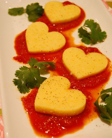 Heart-shaped polenta on pasta sauce. Delicious dinner, serve roasted zucchini, red pepper, onion & eggplant on the side.