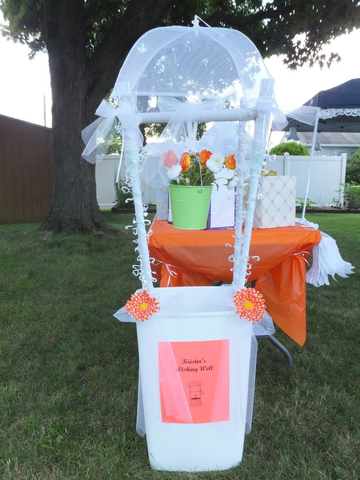 My wishing well my Mom and I made for my bridal shower. All we did was used a trash can for the base and then broom handles and swiffer mops as the four posts. Then we bought a food cover and attached that to the tops of the four posts with string. For the flower bucket in the middle, we took a wrapping paper tube and attached it by cutting the tubes  so they lined up flush to the two diagonal posts and attached it tape. Then we covered the posts with crepe paper and wedding garland.