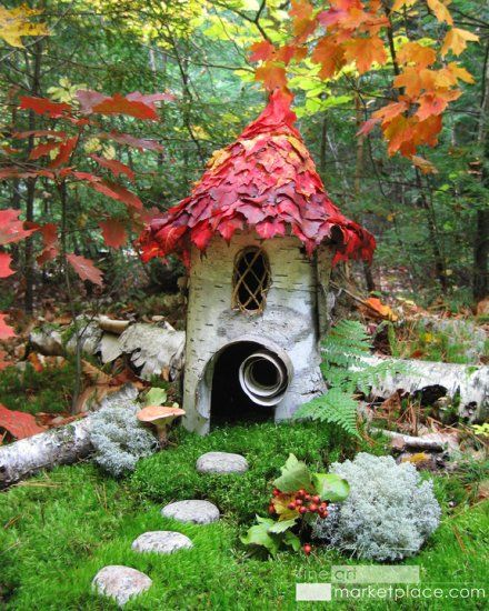A fairy house made of birch bark with autumn leaves for a roof in a deep forest setting.