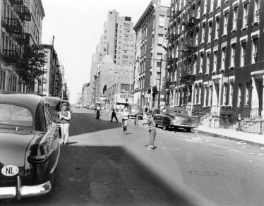 NY baseball the oldschool way, in the street. The view north from 1st Avenue, between 62nd and 63rd Streets, circa 1953.