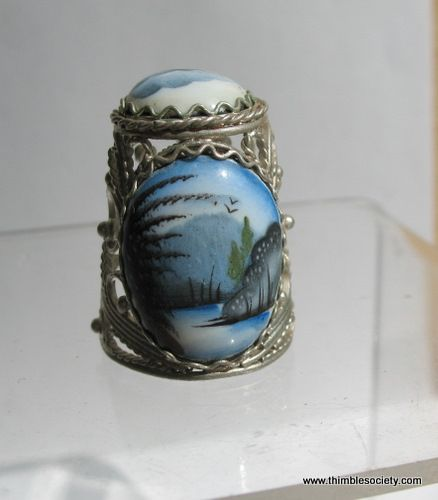 Russian thimble, silver filigree with hand painted porcelain placques. Showing a lake side scene with birds overhead.