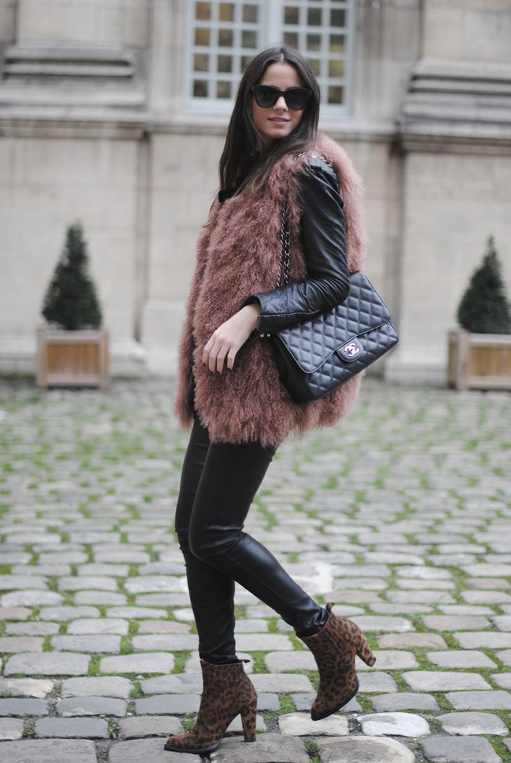 furry vest with leather jacket, leather pants and a pair of leopard boots while holding Chanel bag.