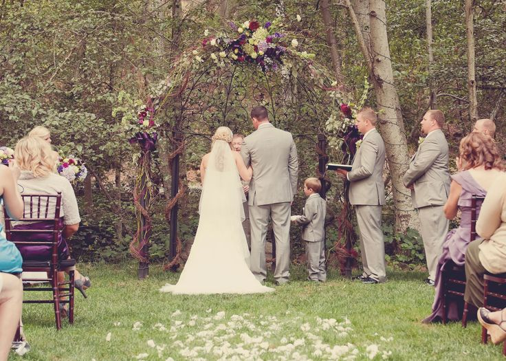 Rustic Wedding Arbor: Decorated with grapevine garland & fresh flowers. The perfect rustic-yet-elegant touch...