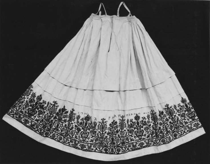 This skirt is signed in embroidered stitches by its maker, Maria Papadopoula, and dated 1757. The top pleated edge is intended to be worn not around the waist but higher, under the arms, held in place by shoulder straps. It is constructed from five loom-widths of a mixed cotton and linen. The opening down the middle of the central width would have allowed room for it to be put on, and also facilitated breast-feeding.