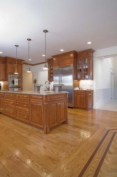 Golden oak cabinets with warm granite looking countertops, white walls