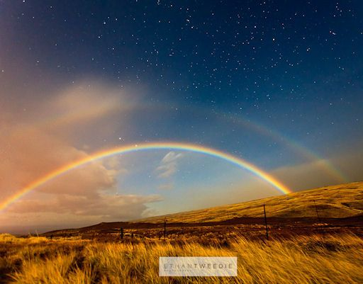"""A RAINBOW AT NIGHT  (3/26/11) Ethan Tweedie of Kamuela, Hawaii, recorded this spectacular example of a rainbow long after dark.    """"It was a moonbow,"""" explains Tweedie. The bright moon played the role of sun, illuminating nightime raindrops falling through the damp Hawaiian air. """"I've been trying to photograph a moonbow for a long time. Last night I was driving back from the Volcano there it was!""""    Tweedie's long exposure revealed something even more rare: a secondary moonbow."""