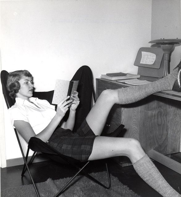 A student lounges while studying in her dorm room, 1950s.