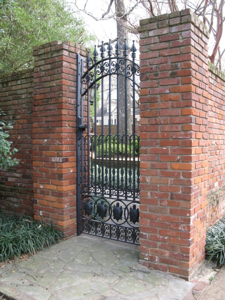 Wrought iron gate set in a brick wall.