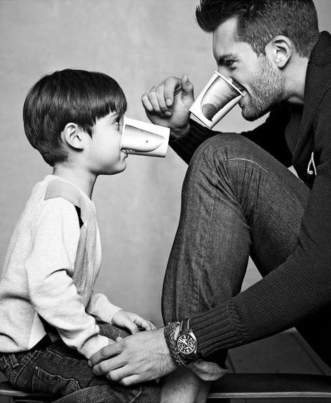 Dad and son Technical: 1. Two light setup; umbrellas or beauty dishes. 2. Composition brings focus to faces. 3. Use of Black / White adds contrast.  Aesthetic. 4. Squatting positions gives feel of equality to both subjects. 5. Light background gives a high key feel.  6. Comical antics adds warmth in a black and white photo. 7. Message: Like father, like son! 8. Great idea for creating levity in a studio portrait session!
