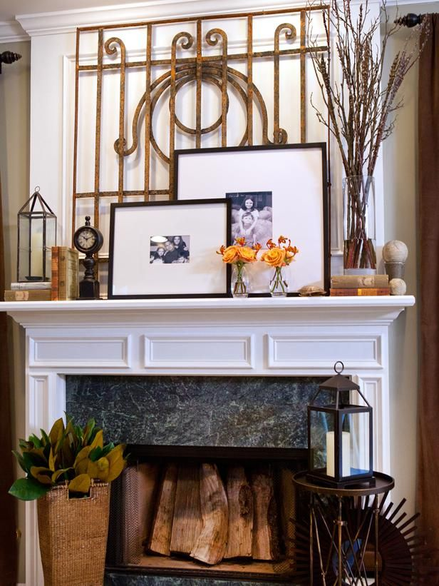 Create a Layered Effect:  A salvaged iron gate creates a textural backdrop for this rustic vignette. Stacks of vintage books, black-and-white photos and a tall glass vase filled with branches complete the look. Overlapping frames always look great on a mantel, especially when they have different orientations — horizontal and vertical.