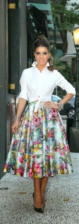 camisa blanca abierta combinada con falda y anudada a la cintura