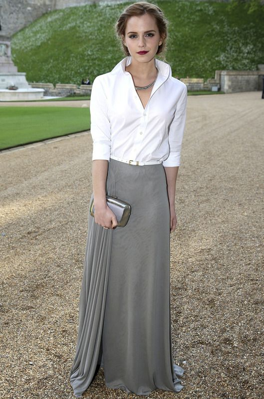 Emma Watson con un look de Ralph Lauren Otoño 2014 compuesto por una falda larga gris con detalle plisado en el lateral y una camisa blanca con fino cinturón a juego. Le añadió un clutch metalizado de Roger Vivier, un collar rígido y un look de belleza muy romántico.