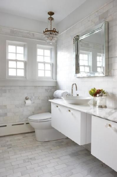 House & Home    Gorgeous white chic bathroom design with antique brass crystal chandelier, square beveled mirror, overmount round sink, modern floating double vanities with white carrara marble counter tops, glass knobs hardware, white carrara marble subway tiles floors & backsplash and chrome fixtures.