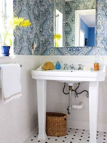 My favorite color blue beautifully represented in the patterned wallpaper of this traditional, yet inviting bathroom.  Furthermore, an oversized porcelain sink that can hold all the cleansing necessities, a classic black and white tiled floor and a clever transition to white subway tiled demi walls; makes for one lovely bathroom.