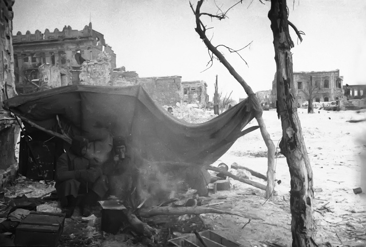Two Soviet soldiers seek protection under a tarpaulin in the streets of Stalingrad. The battle is over (Feb 1943) but conditions for the victors haven't improved other than the absence of combat ( a major plus).