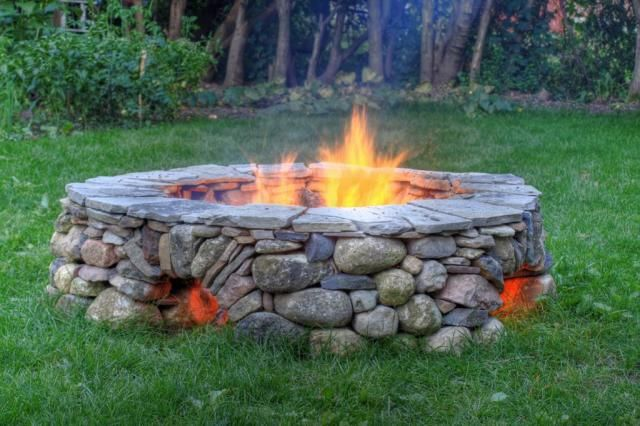 Firepit with openings at the bottom for airflow and keep feet warm.