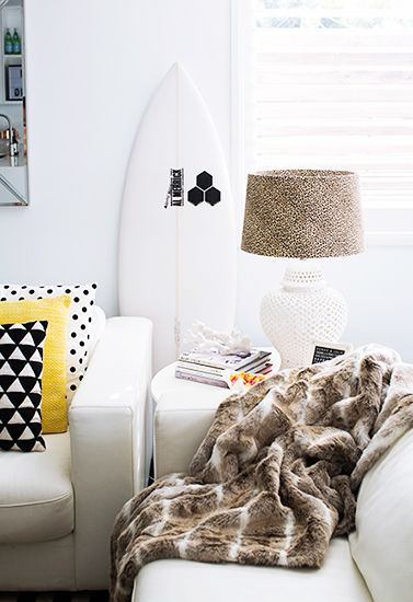 21 Homes That Prove Surf Is Chic // surfboards as decor // white surfboard, living room, white leather sofas, fur throw, leopard-print lampshade
