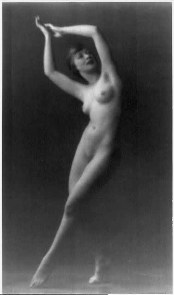 [Nude woman, full length, standing, facing right; hands raised above head]    no date Photo by Arnold Genthe.