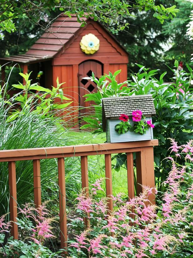 Gorgeous garden beds and a wee porch set off this playhouse.