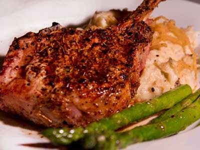 Prime Pork Steak laid over mashed potatoes with caramelized onions and ...
